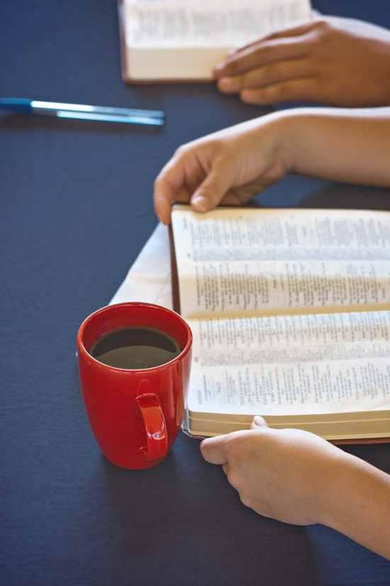 open bible and mug of coffee on table